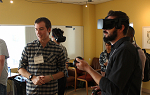 A Landmark College student helps a participante try out a virtual reality educational game
