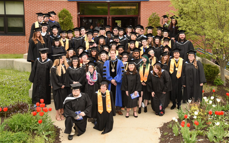 Spring 2017 graduates with Dr. Peter Eden outside the Click Family Sports Center in their academic regalia