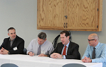 Three superintendents and Landmark College President Peter Eden sit at table while one superintendent signs memorandum of understanding