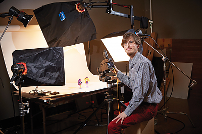 Landmark College student sits in front of photography studio during Hasbro, Inc. internship.