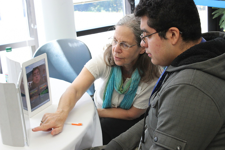 An LCIRT presenter works with a student on an iPad