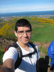 Selfie by Ben Lachman with ocean and green hill in background