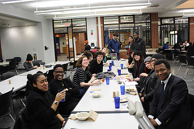 A long table shot of students who participate in Center for Diversity and Inclusion programming gathering for dinner in the Dining Hall.