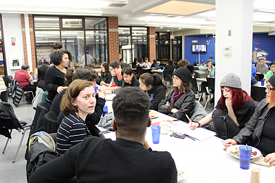 Another long table shot of students who participate in Center for Diversity and Inclusion programming gathering for dinner in the Dining Hall. This time, they are engaged in conversation rather than posing for a picture.