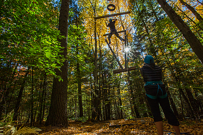 Landmark College student ascends ropes challenge course with spotter watching on.