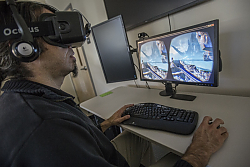 Dr. Ibrahim Dahlstrom-Hakki of LCIRT wears virtual reality headset while computer monitor shows scene that he is viewing