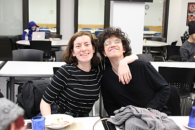 A female student and a male student smile for the camera during a dinner for students who participate in Center for Diversity and Inclusion activities. The female student on the left has her arm around the male student.