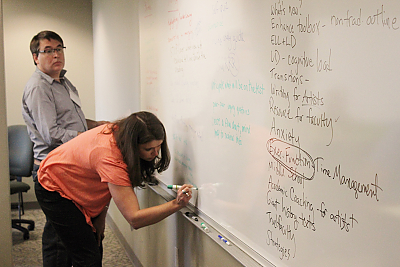 Participants in a LCIRT workshop working together on a whiteboard.
