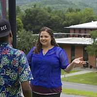 Rachel Brown stands on upper campus talking to another student