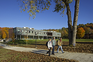 Three students walk down path in front of MacFarlane Center with fall colors on trees in background
