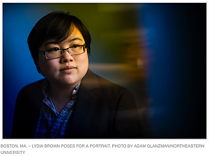 Headshot of Lydia Brown, young East Asian person, with stylized blue and yellow dramatic background. They are looking in the distance and wearing a plaid shirt and black jacket. Photo by Adam Glanzman.