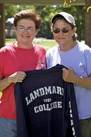 Two women at Landmark College holding a Landmark College t-shirt