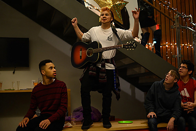 A scene from the 2019 Pose Party organized by the Stonewall Center. A student with a guitar is standing on a bench with his arms raised up as if he's making an annoucment. Several students seated on the bench are looking at him.