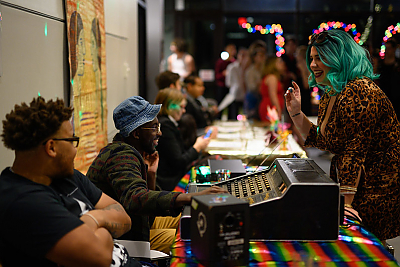 A scene from the 2019 Pose Party organized by the Stonewall Center. A student wearing a bright green, long-haired wig is talking to an African American male student who is seated behind a sound mixer.