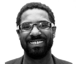Black and white Headshot of Dr. Ousmane Power-Green, African-American male with beard, glasses, and a warm smile.