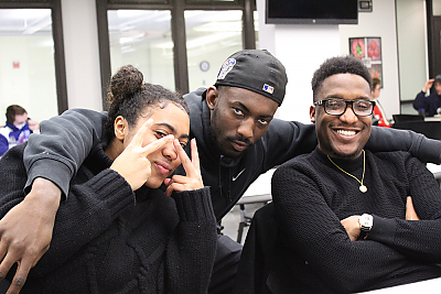 Three African-American students pose for a picture. A female student on the left is making V-signs with both her hands and hold them near her eyes. A male student in the middle is stooping down with his arms around the other two. The student on the right has his arms folded and he is smiling brightly.