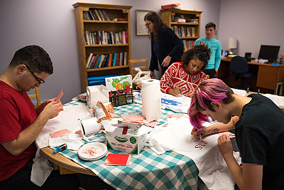 A group of students sit around a table in the Center for Women and Gender. The are making t-shirts with empowering slogans for Sexual Harassment Awareness Day.
