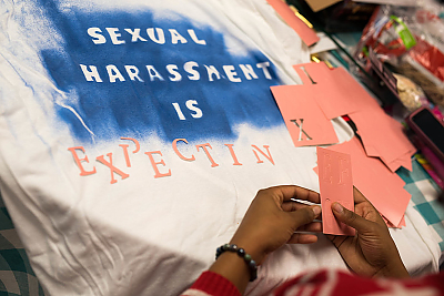 A close-up of one of the stencils being put on a t-shirt during the 2017 Sexual Harassment Awareness Day activity. The words, which are in white on a blue background, read