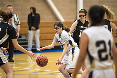 Landmark College women's basketball team player dribbling ball.