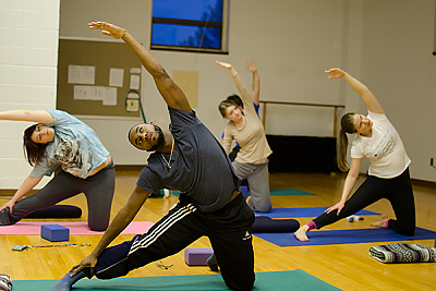 Landmark College students do a side stretch during a yoga class.