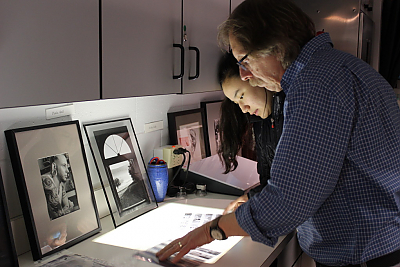 Kosiba and student look at negatives on light box