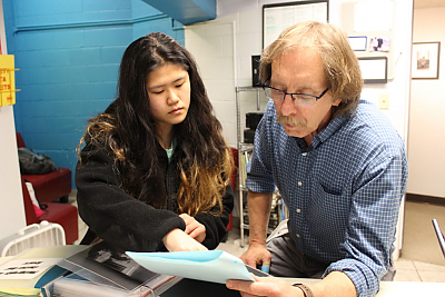 Kosiba looks at portfolio with student