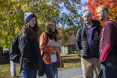 Four Landmark College students stand outdoors with fall foliage in background