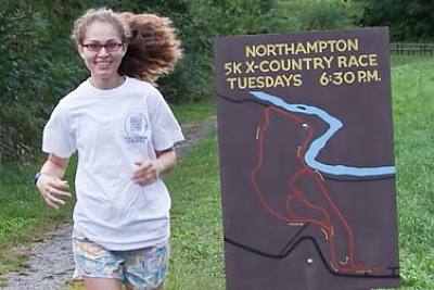 Landmark College Cross Country runner jogging along trail in Northhampton 5K race