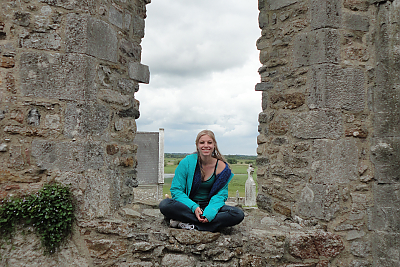 Landmark College student sitting in an archway at Clonmacnoise