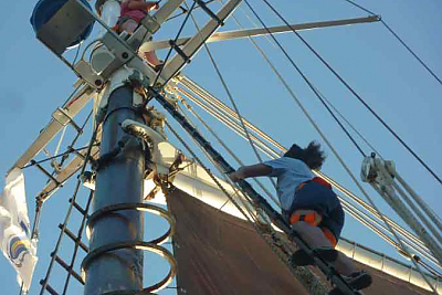 Student climbs rigging on ship