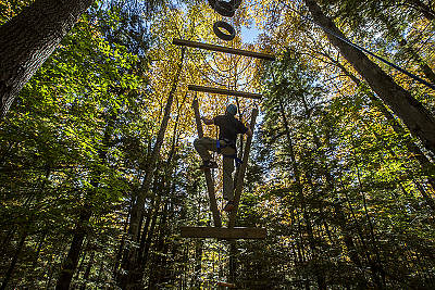 A student climbing the ropes course in the woods at Landmark College