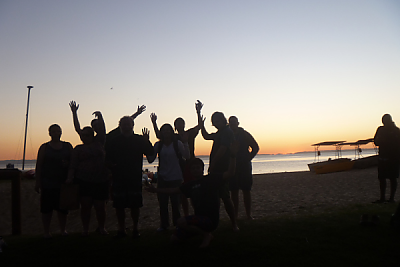 Silhouette of Australia program participants waving with sunset in background