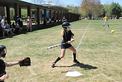 A girl swinging at a pitch during a softball game.
