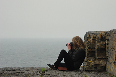 Student taking picture while sitting at the edge of the Cliffs of Moher