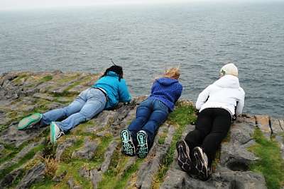 3 Landmark College students looking over the cliffs of Moher.