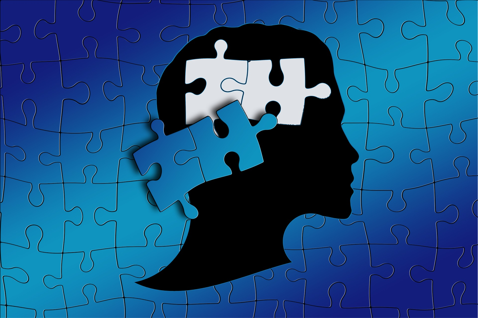 A puzzle of a person's silhouette with two pieces removed from area where brain would be.