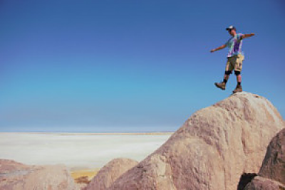 Man walking and balancing on top of sandstone hill