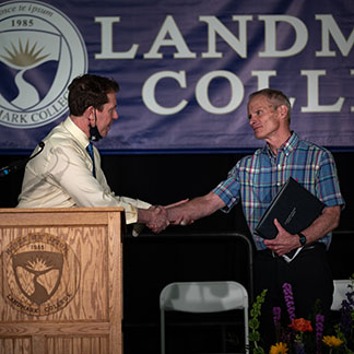 Dr. Peter Eden, president of Landmark College (left), shakes hands with professor emeritus Jim Baucom (right) after presenting him with an honorary Doctorate of Humane Letters degree during a faculty and staff retirement ceremony held on May 22, 2021. Baucom was a founding member of the College's faculty and served as its first Academic Dean. He retired at the end of the Spring 2020 semester after a 35-year teaching career at the College. (Photo credit: Todd Miller)