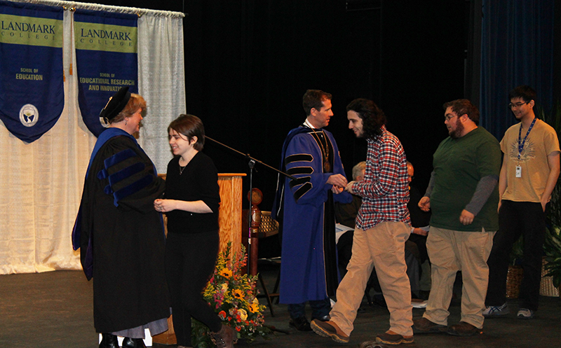 New students proceed across stage to receive coin from Landmark College president Dr. Peter Eden and Vice President of Academic Affairs Gail Gibson Sheffield during 2019 Convocation