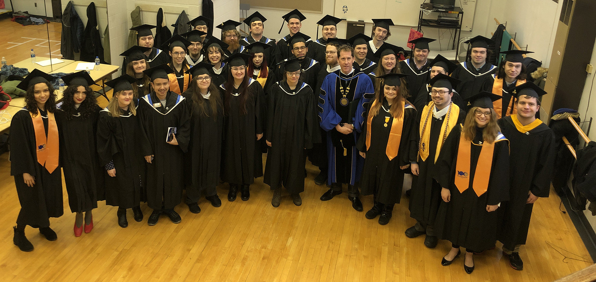 A photo of the Fall 2019 Class wearing their graduation caps and gowns, taken backstage with Landmark College President Dr. Peter Eden just before the December 14, 2019 Commencement Ceremony.