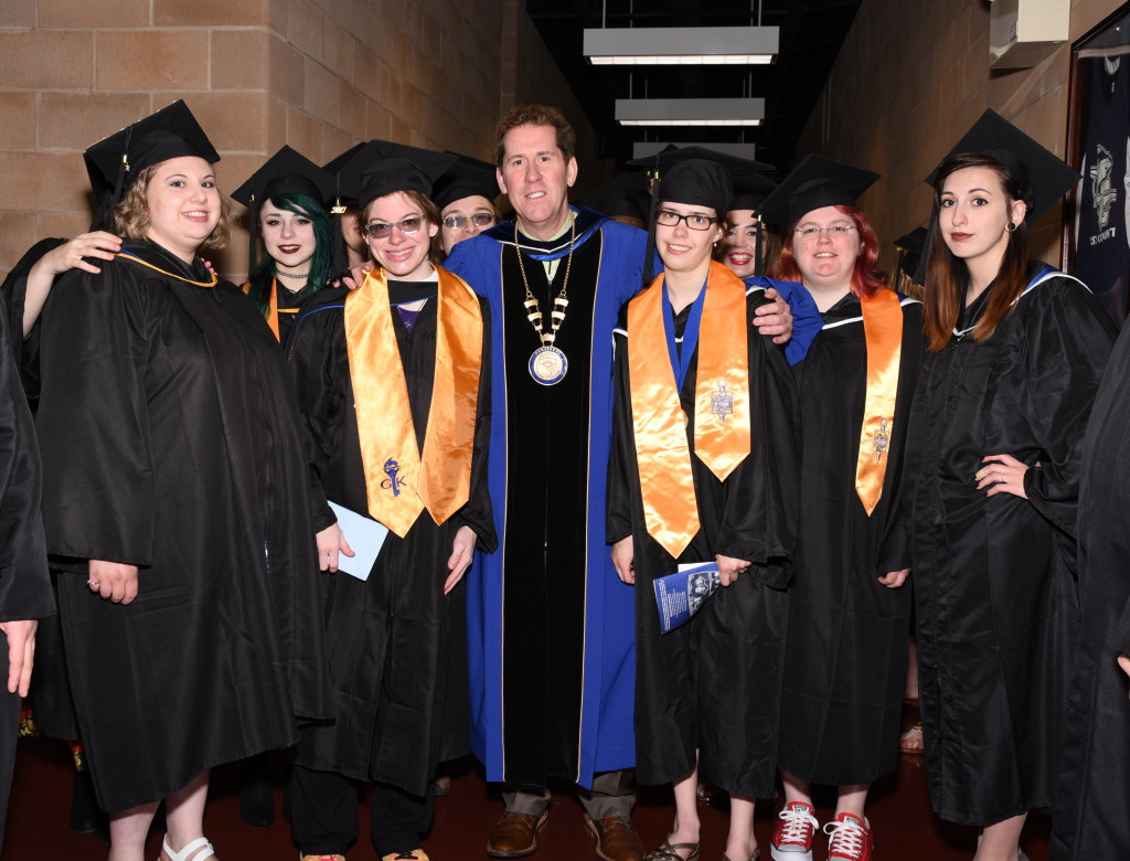 Graduates in academic regalia in the Click Family Sports Center with Peter Eden