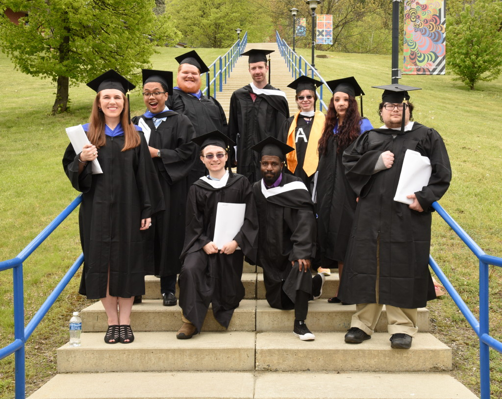 Students in academic regalia standing on steps to upper campus