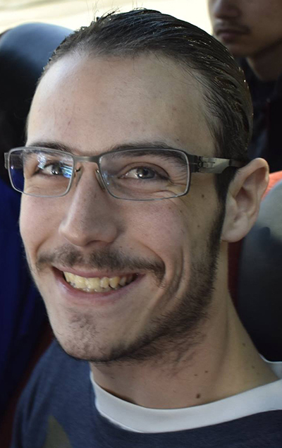 A close up of Micah looking at the camera and smiling. He has very short brown hair and a wispy mustache. He is wearing glasses and blue shirt on top of a white t-shirt.