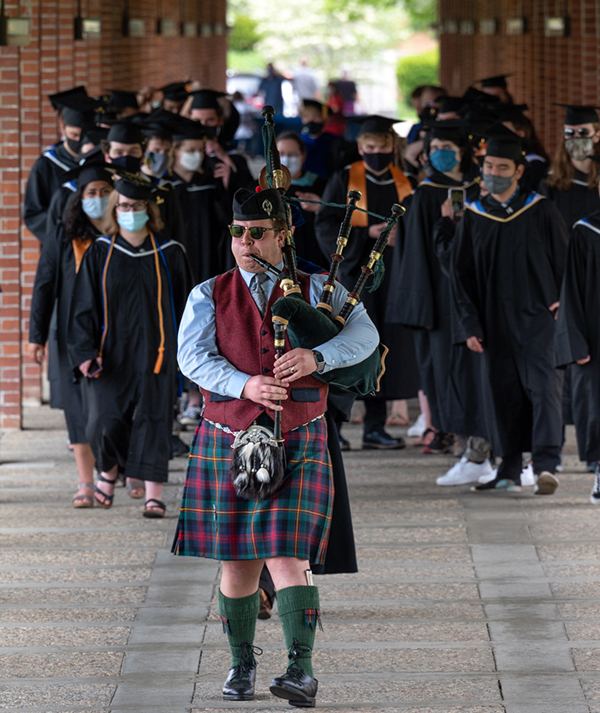 A man in kilt playing bagpipes leads students wearing graduation caps and gowns toward graduation stage