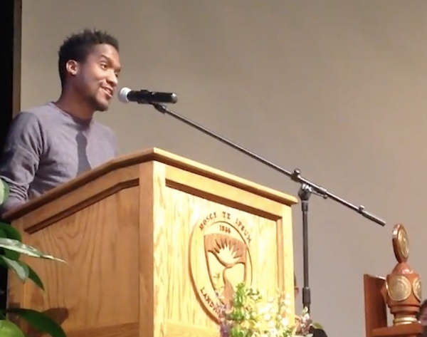 Alumnus Marc Thurman '18 speaking into a microphone at a podium with the Landmark College emblem.
