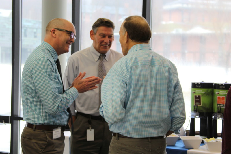 Three superintendents stand and talk in Cafe Court at Landmark College