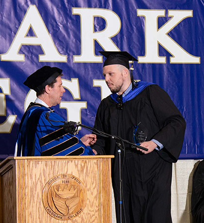 Connor Lawrence shakes hands with Landmark College president Dr. Peter Eden after accepting the President's Award during the 2019 Spring Commencement ceremony