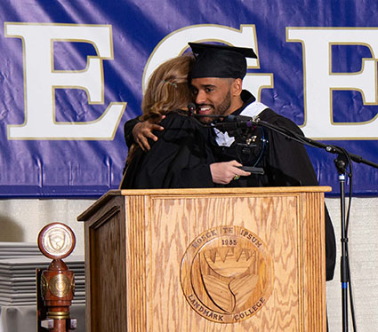 Isaac Alam shares and embrace with Dean of Students Kelly O'Ryan after accepting the Community Service Award during the 2019 Spring Commencement ceremony.