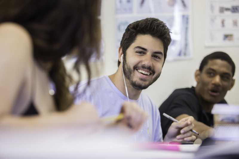 Student holds pen and smiles at another student while a third student looks on