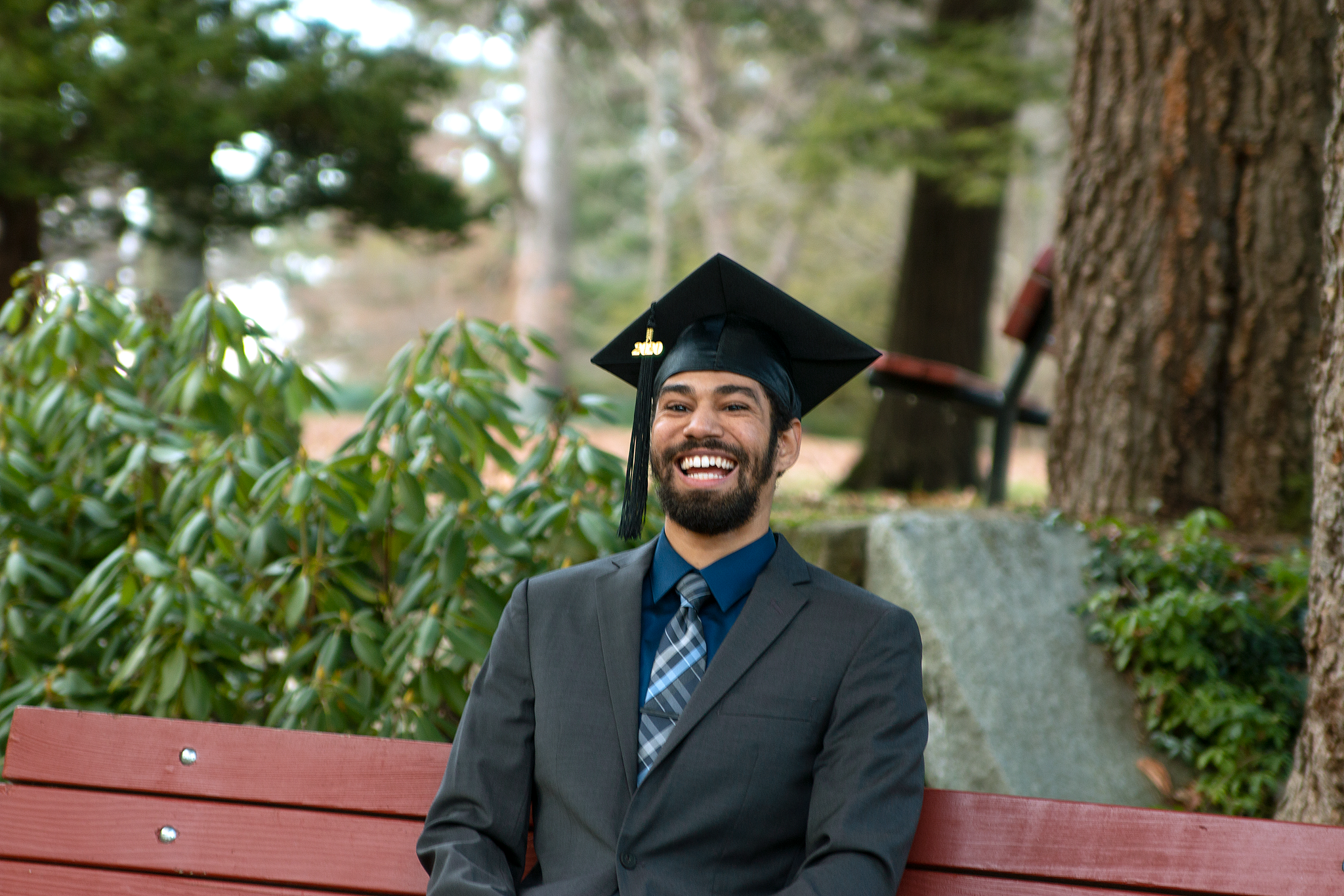 Student smiling while sitting outdoors on bench with jacket, tie and graduation cap.